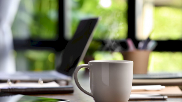 A hot and steaming cup of coffee on a desk with laptop and gadget when work from home